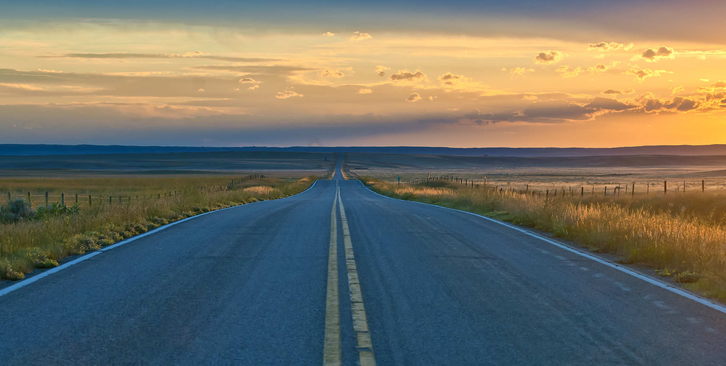straight road disappearing into distance on horizon with sunset. Sunburst, MT