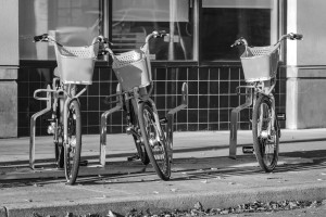 Grayscale image of bike share bicycles stored in bike rack