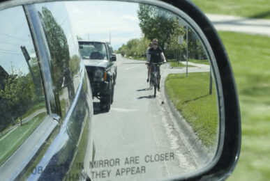 Passenger side-view mirror of car showing two cyclists riding along curbside.